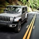 A silver 2019 Jeep Wrangler, popular among used Jeeps for sale, is driving on a tree-lined road.