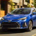 A blue 2019 Toyota Corolla, which is popular among used cars in Columbus, Ohio, is driving past a blurred building.