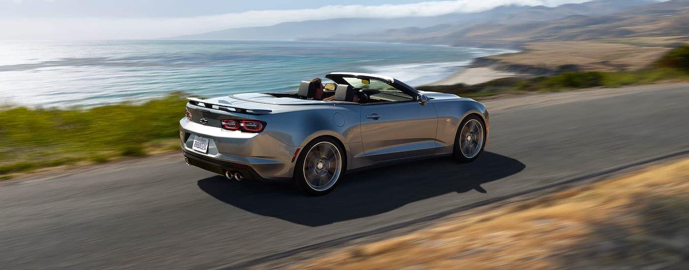 A silver 2020 Chevy Camaro convertible is driving along the coast.