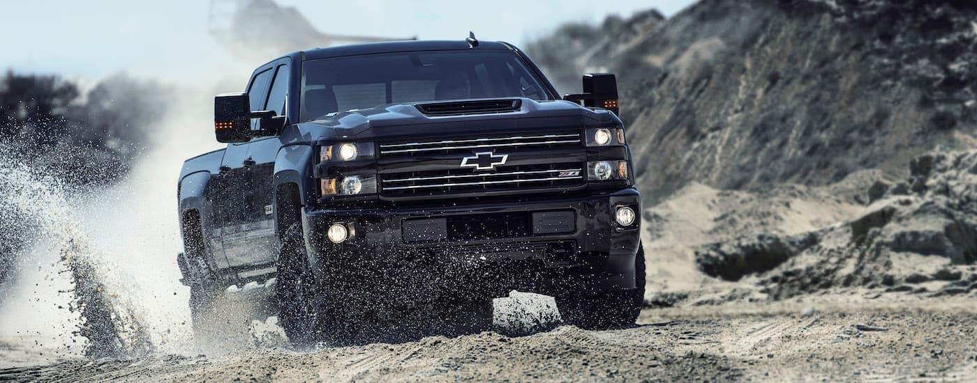 A black 2017 Chevy Silverado 2500HD is off-roading in sand.