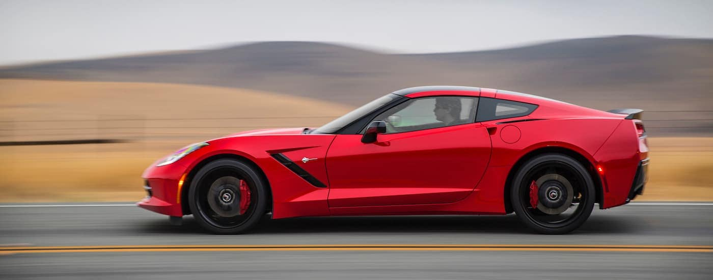 A red 2018 Chevy Corvette is shown from the side driving past distant hills in Indiana.