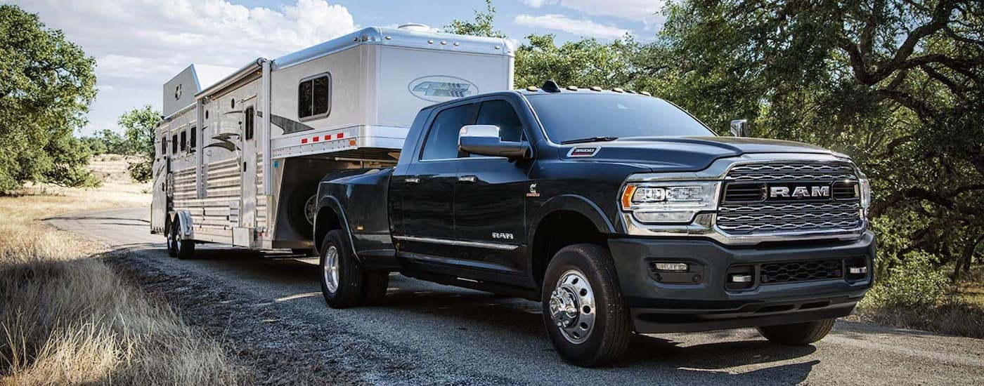 A black 2019 Ram 3500 is towing a gooseneck trailer on a back road in Kentucky.