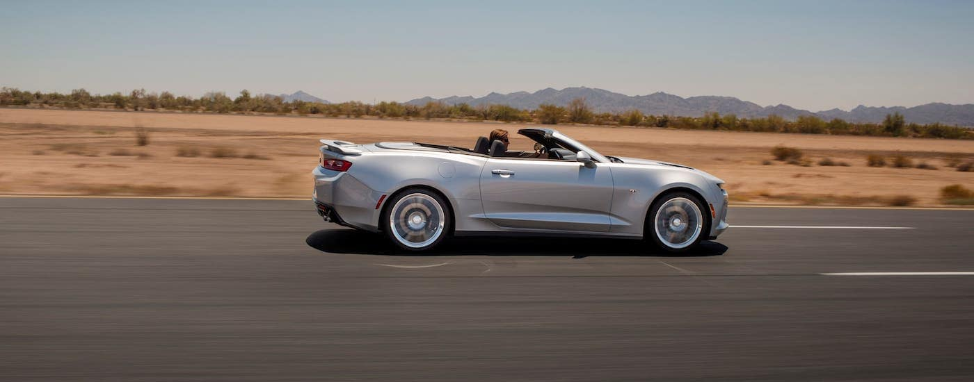 A silver 2018 Chevy Camaro convertible is shown from the side driving on an empty highway.