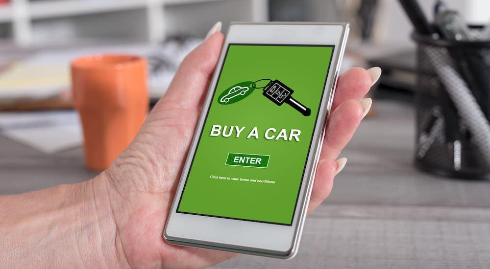 """A woman's hand is holding a cell phone and reads """"buy a car"""" as she shops at an online car dealer."""