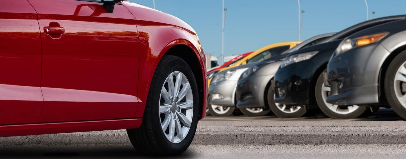 Rows of cars are shown on a dealership lot.