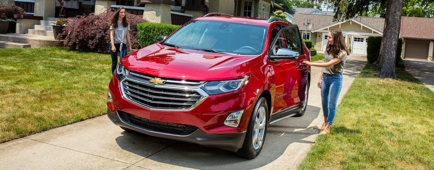 Two teens are about to get into a red 2018 Chevy Equinox.