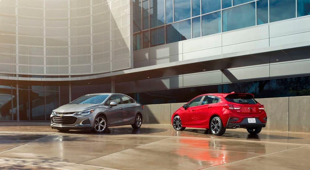 A gray 2019 Chevy Cruze sedan and a red hatchback are parked in front of a Louisville used car dealer.