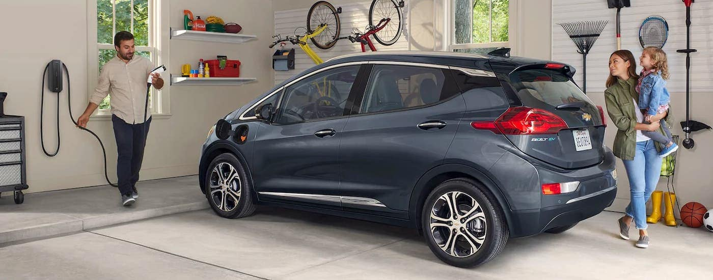 A family is walking away from a gray 2020 Chevy Bolt EV in a garage.