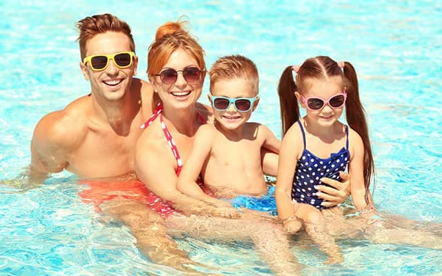 Family of four in shallow pool
