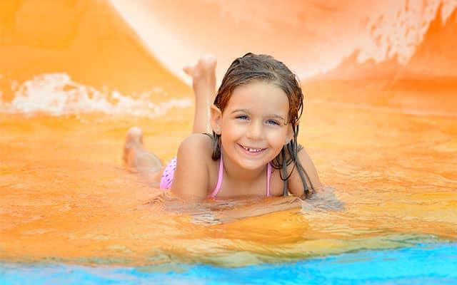 Girl posing in water by slide
