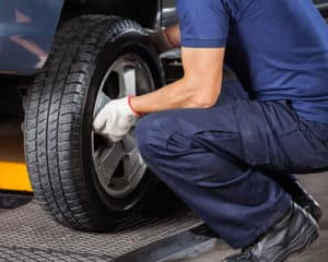 Low section of mechanic fixing car tire at auto repair shop