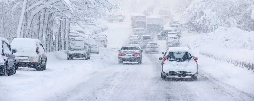 Cars on a snowy and icy road in winter with an accident