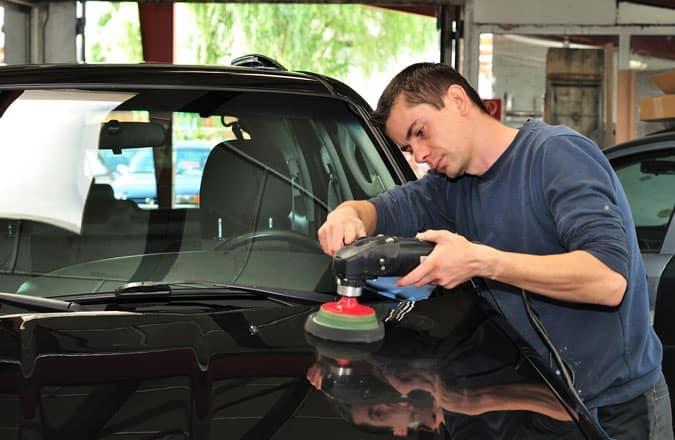 Shop technician polishing the hood of the car