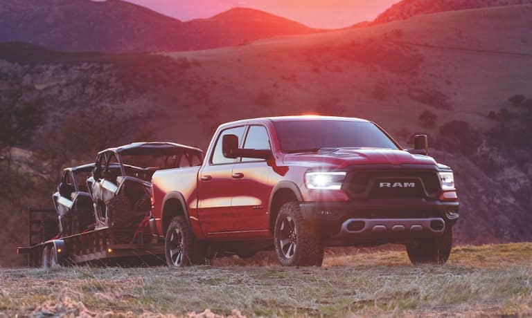 Red Ram 1500 towing boats over a hill at sunset