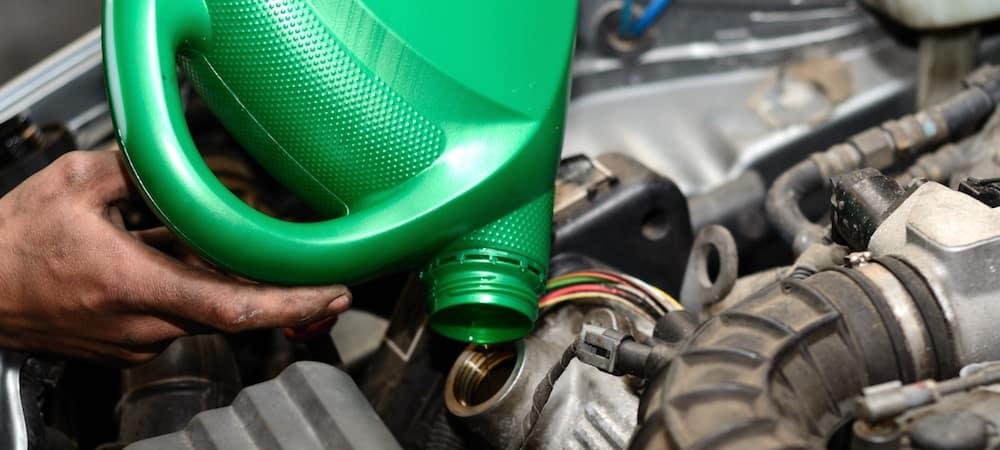 Car mechanic changing oil