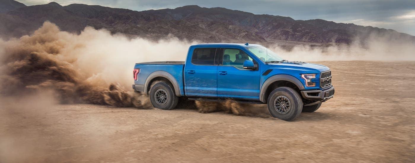 A light blue 2020 Ford F-150 Raptor is kicking up dirt in a desert.