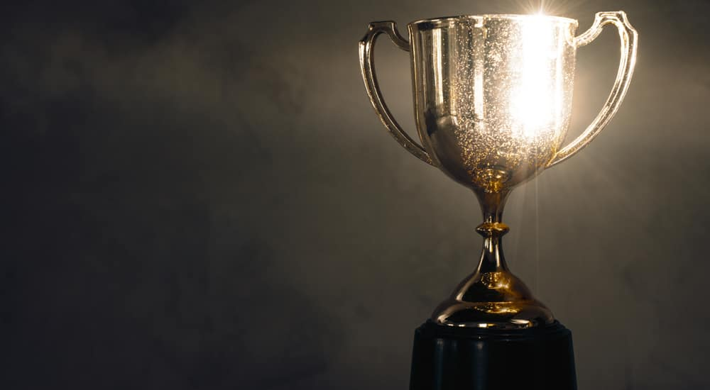 Gold, glowing trophy against a black background