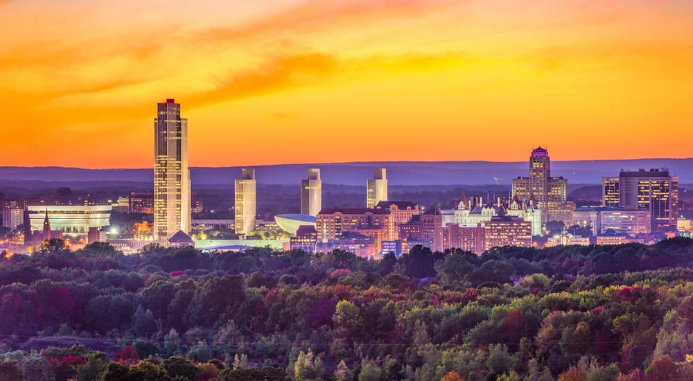 Skyline of Albany NY in front of an orange sunset