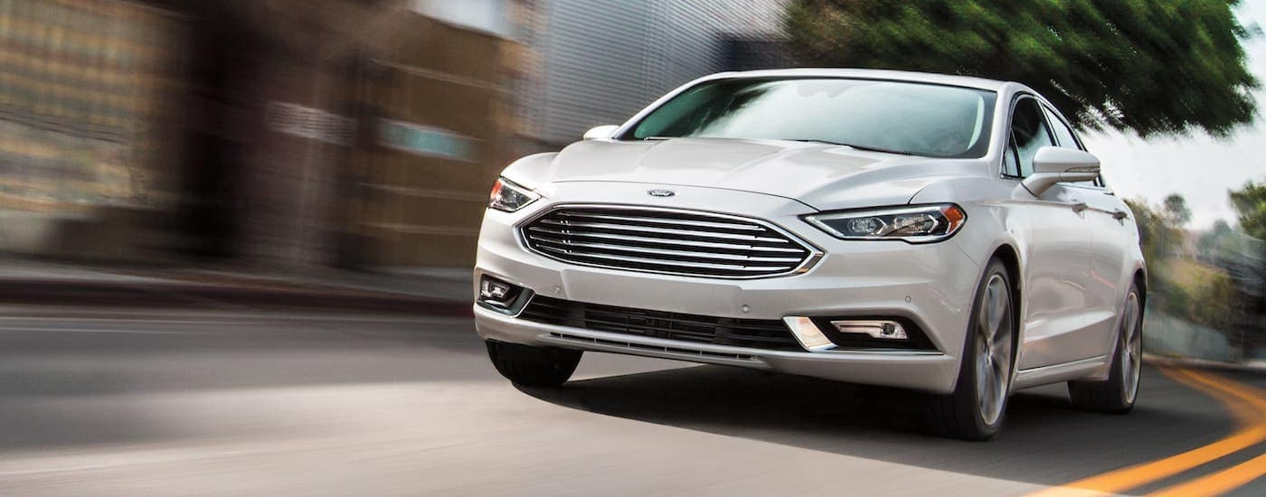 A white 2020 Ford Fusion is driving on a city street after leaving a Ford dealership near you.