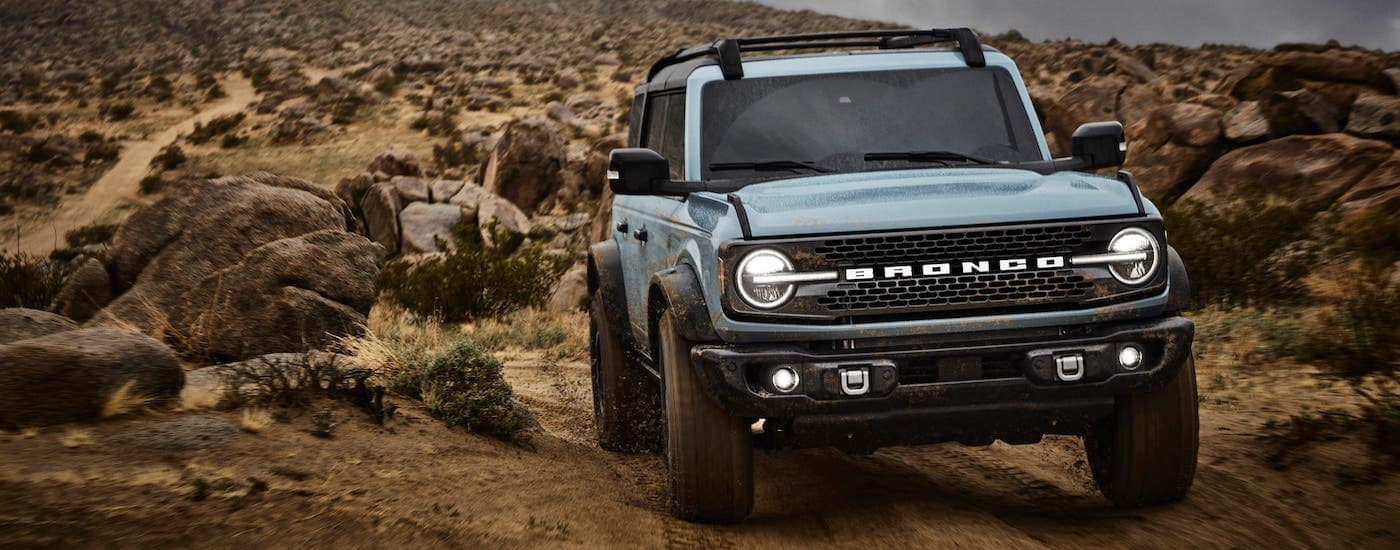 A pale blue 2021 Ford Bronco 4-door is shown from the front driving on a rocky trail.
