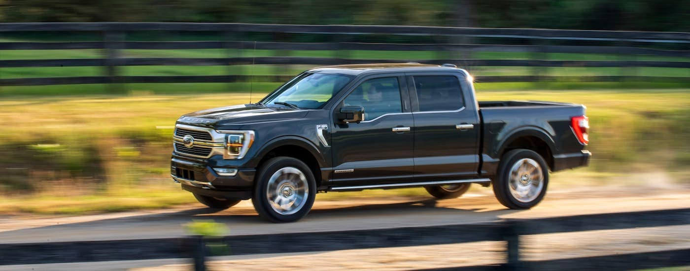 A black 2021 Ford F-150 is driving in front of a black fence.