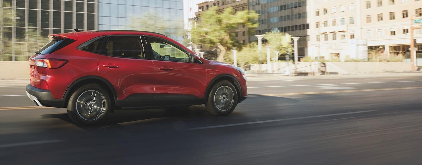 A red 2021 Ford Escape is shown from the side driving on a city street.