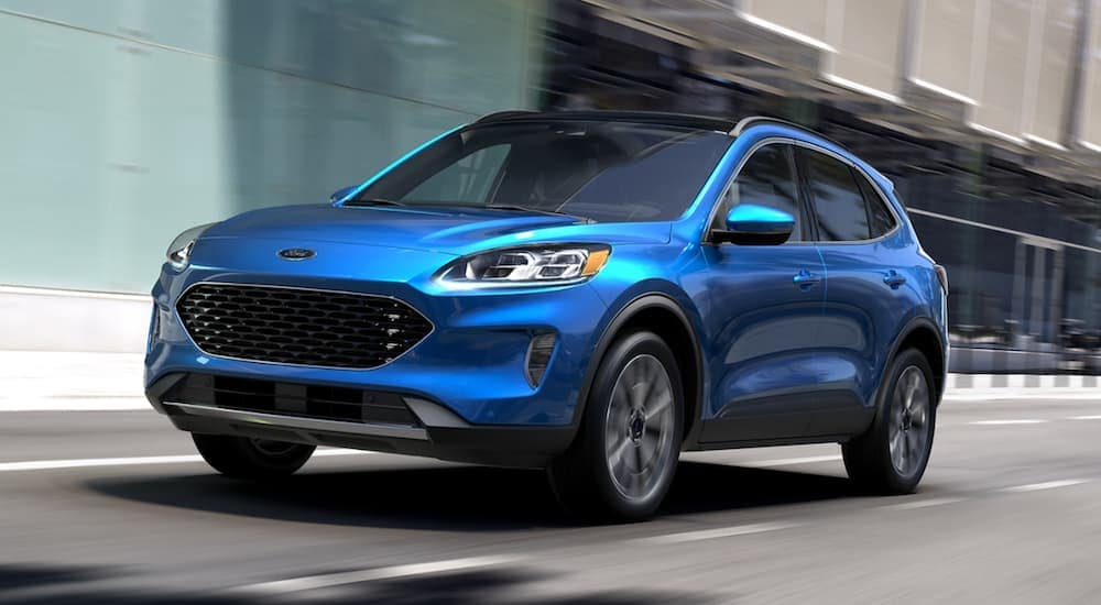 A blue 2020 Ford Escape is driving past a city building.