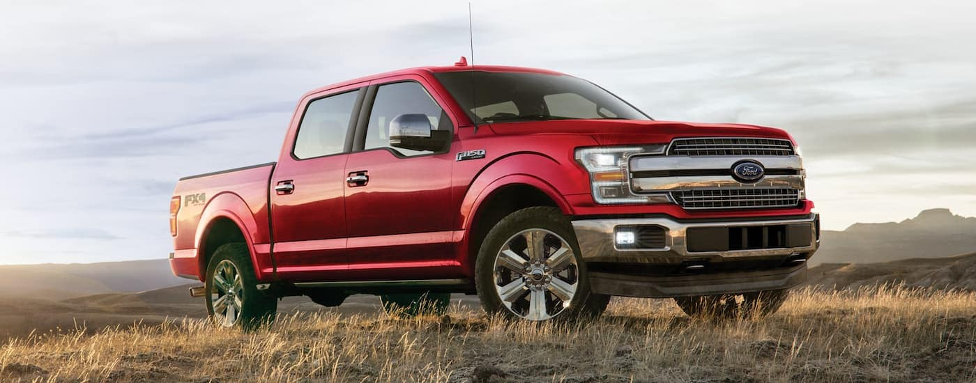 A red 2020 Ford F-150 is parked in a field with mountain views after leaving a Ford dealership near me.
