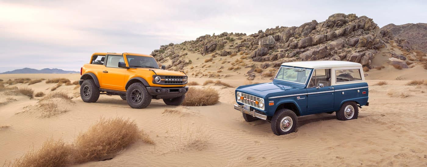 A yellow 2021 Ford Bronco is parked next to a blue first-generation Bronco in a sandy dessert.