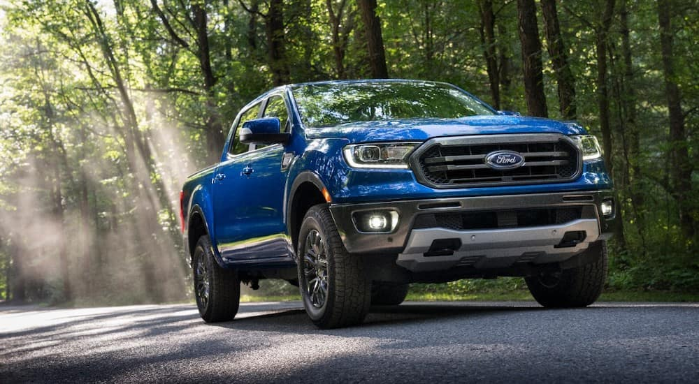 Blue 2020 Ford Ranger truck driving past green trees on a paved road
