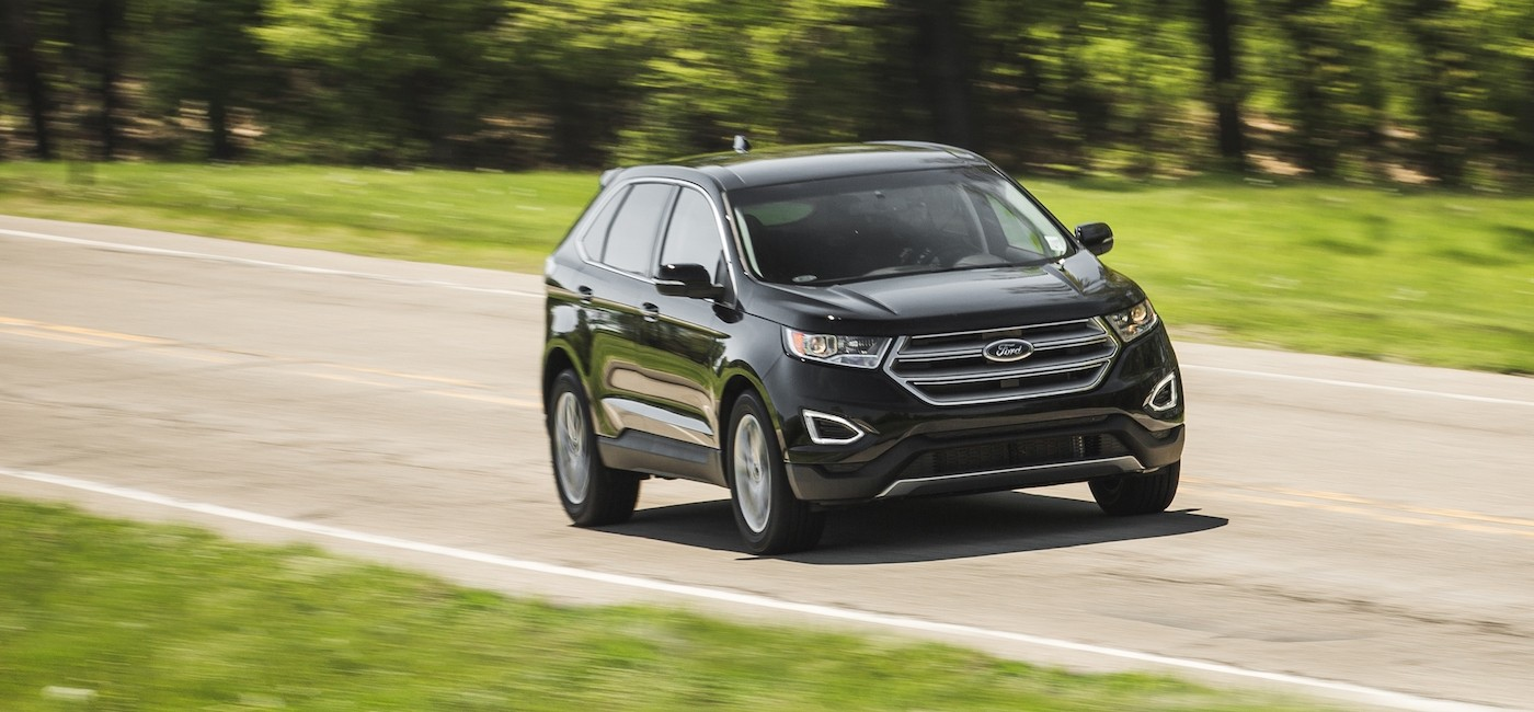 A black 2017 Ford Edge is driving on a grass-lined road near Albany, NY.