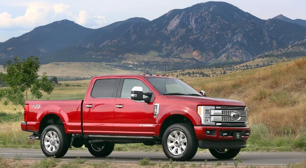 Red 2017 Ford F-250 Super Duty pickup truck parked on a paved road with green fields and dark mountains in the distance