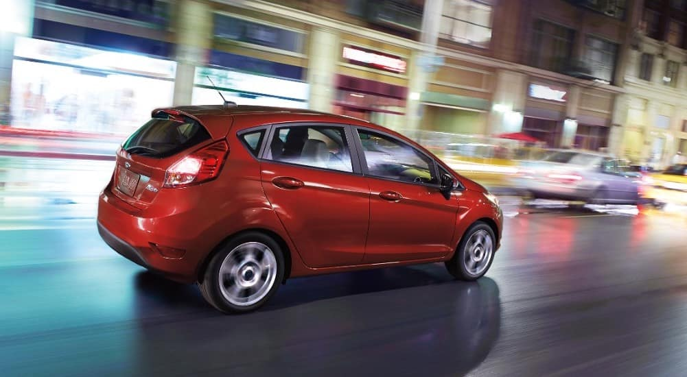 Red 2018 Ford Fiesta hatchback driving down a road next to store fronts
