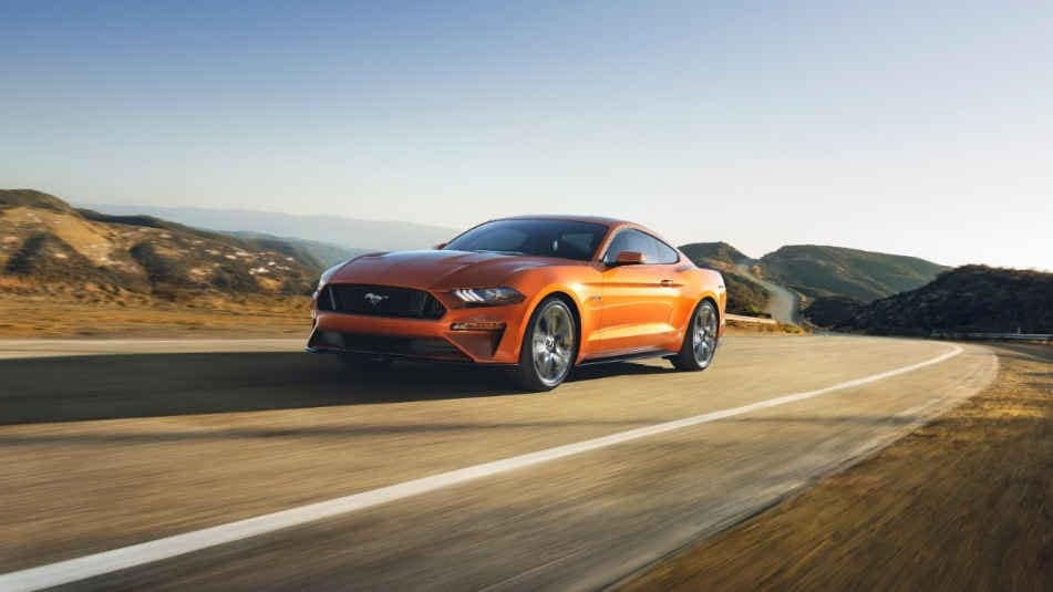An Orange 2018 Mustang Driving around a curve