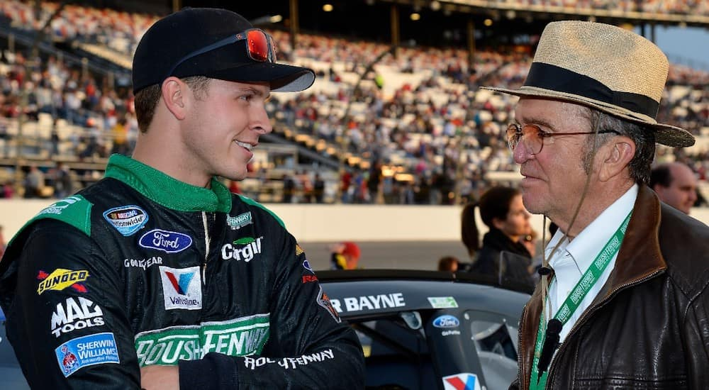 Jack Roush wearing a hat standing next to NASCAR driver at a stadium with an audience in the background