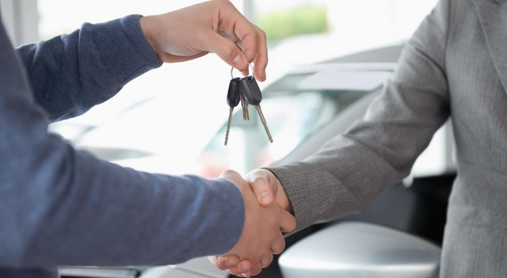Two hands are shaking inside a Ford Dealership near Troy, NY, while one of the hands is holding car keys.