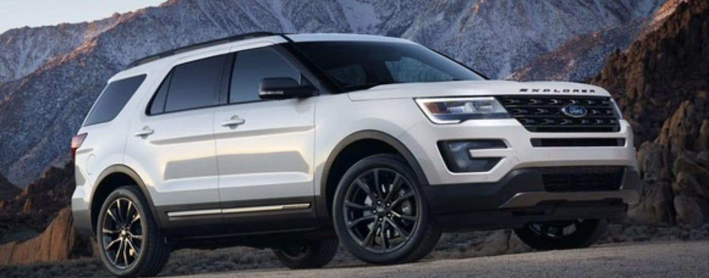 A white 2018 Ford Explorer is parked in front of snowy mountains near Albany, NY.