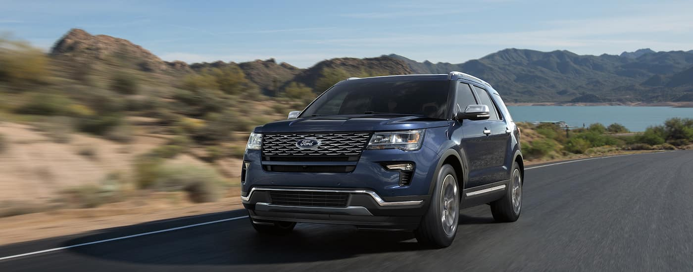 A blue 2018 Ford Explorer is driving away from a lake and mountains.