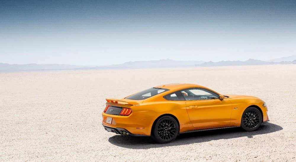 Orange 2018 Ford Mustang parked on flat, light colored ground with mountains in the distance