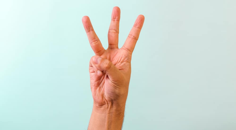 Hand with three fingers up in front of a blue wall