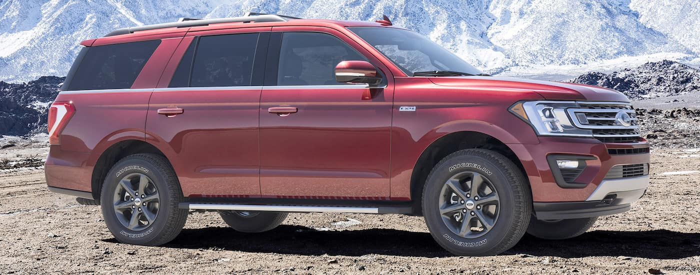 A red 2018 Ford Expedition is parked off-road with a blue sky and clouds above it.