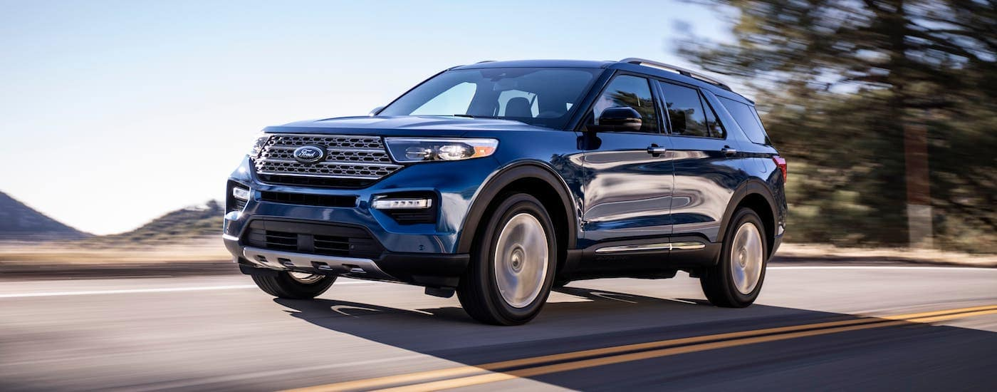 A dark blue 2020 Ford Explorer is driving on a road near Albany, NY.
