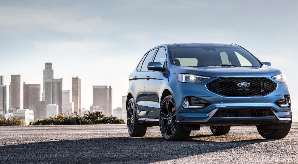 Blue 2019 Ford Edge SUV parked on cement in front of a city skyline