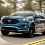 Blue 2019 Ford Edge SUV driving on a blue and yellow paved road past green trees