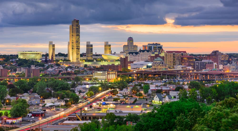 Lit-up Albany NY skyline with a sunset behind it