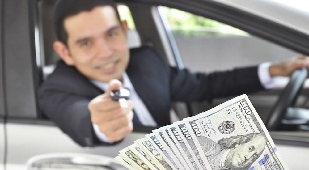 A car salesman is holding a car key out of a car window while someone hands him cash.