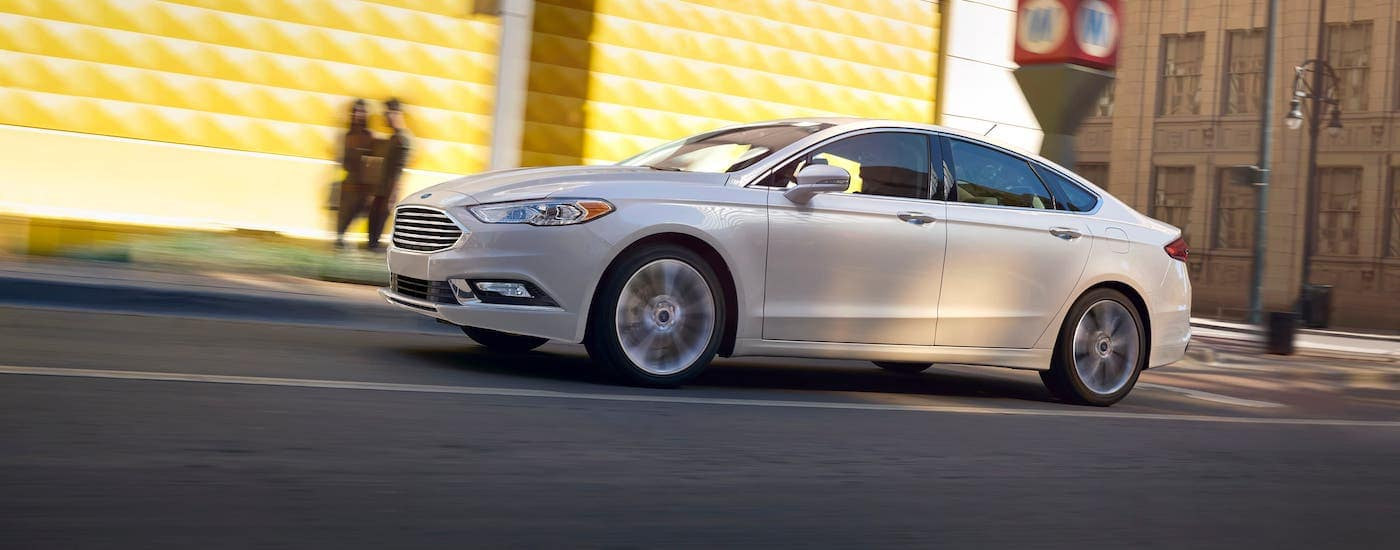 A white 2017 Ford Fusion is driving on a city street near Albany, NY.