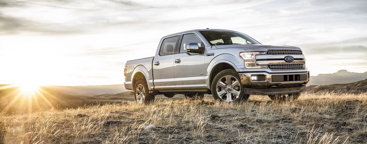A vehicle that holds its used car value, a silver 2018 Ford F-150 is parked in a field in front of the sun.