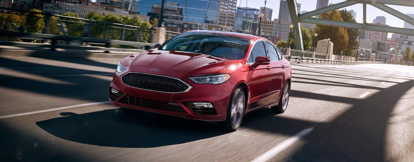 A red used 2017 Ford Fusion is driving over a bridge away from a city.