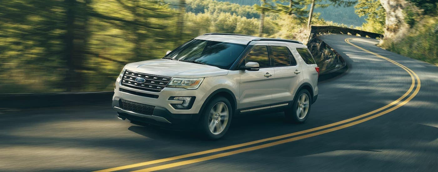 A common used car for sale, a white 2017 Ford Explorer is driving on a winding forest road near Albany, NY.